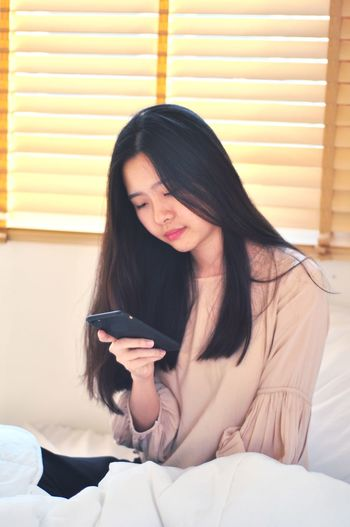 Young woman using phone while sitting on bed