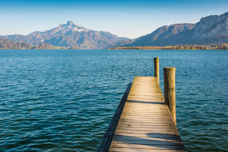 Wooden pier in lake against mountains