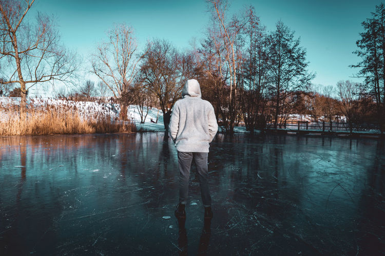 Rear view of man standing by lake against sky during winter