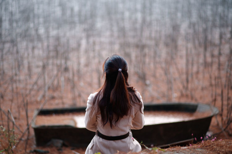 Rear view of woman sitting in forest