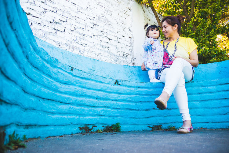 Low angle view of mother and daughter sitting in park