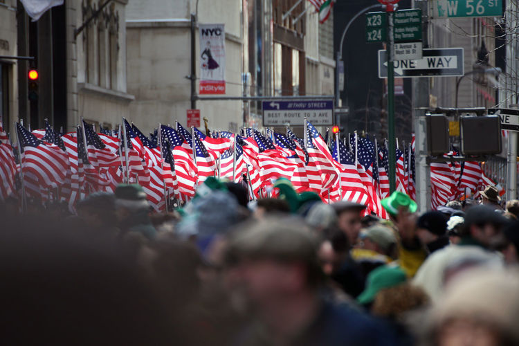Crowd With American Flags By Buildings In City