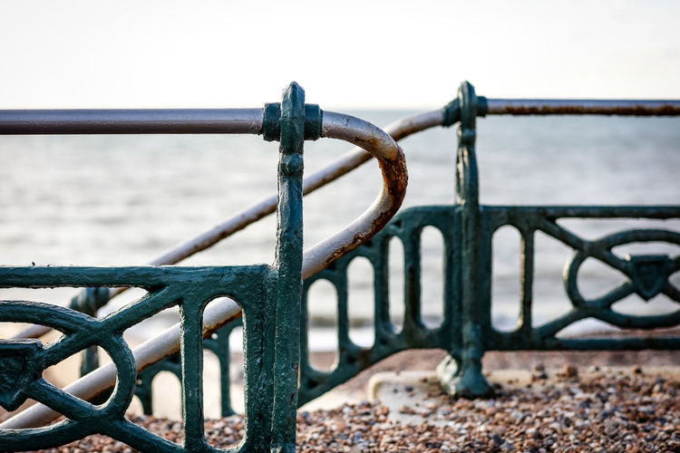 Close-up of railing by sea against clear sky