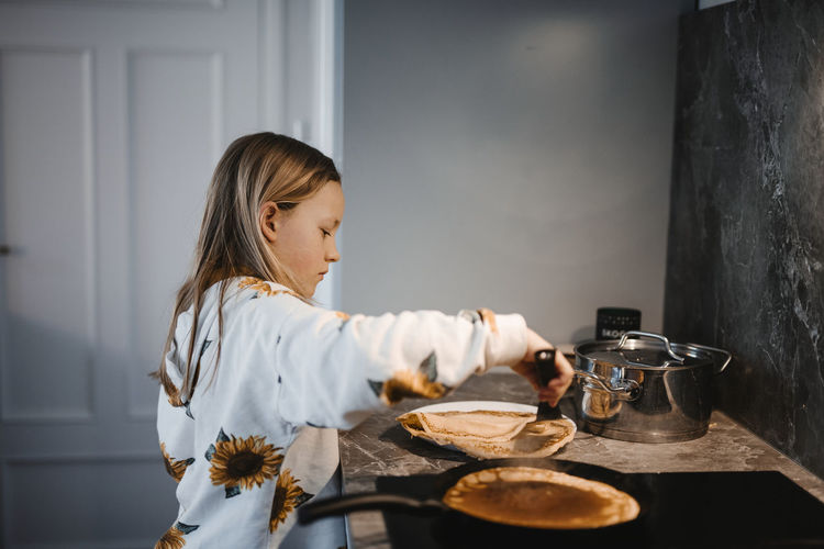 Side view of girl holding food on table at home
