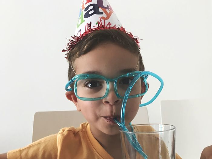 Portrait of boy in party hat having drink through strawglasses against wall at home