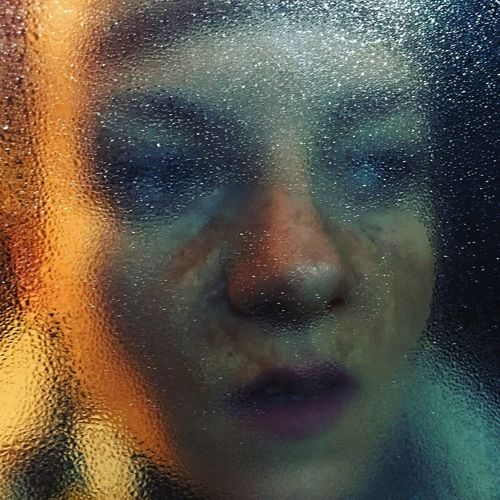Close-up of thoughtful woman seen through window