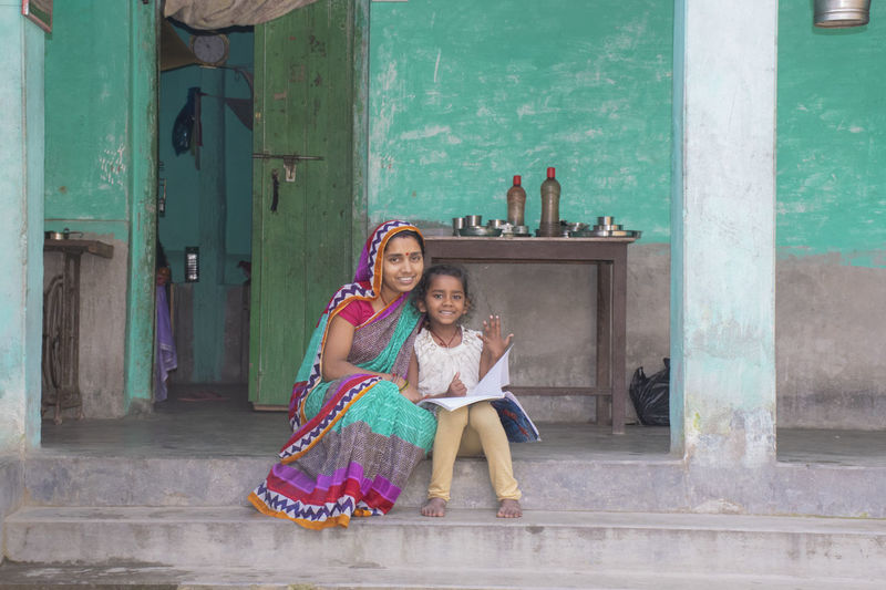 Portrait of smiling mother and daughter reading book in courtyard of the house in village india