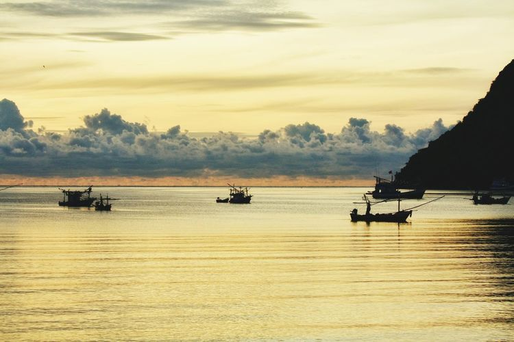 Silhouette boats sailing in sea against sky during sunset