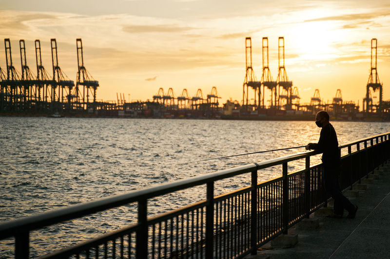 Silhouette man looking at pier against sky during sunset