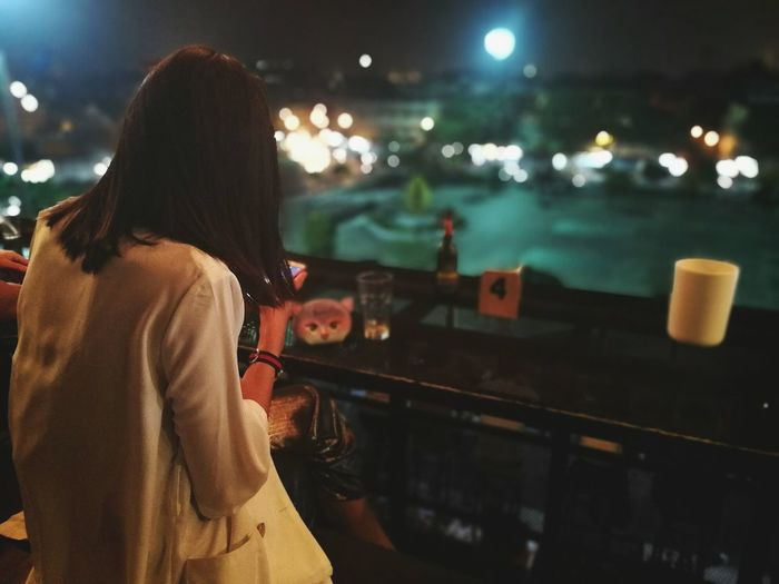 Rear view of woman sitting in restaurant at night