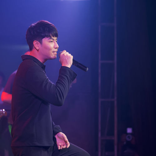Side view of young man standing at music concert
