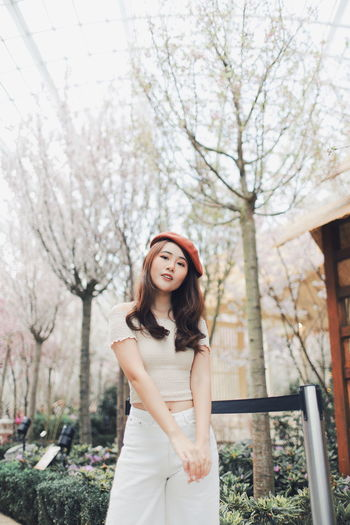 My Best Photo International Women's Day 2019 Streetwise Photography One Person Young Women Tree Young Adult Standing Looking At Camera Front View Women Smiling Leisure Activity Beautiful Woman Real People Focus On Foreground Plant Three Quarter Length Lifestyles Portrait Casual Clothing Adult Hair Hairstyle Fashion Outdoors
