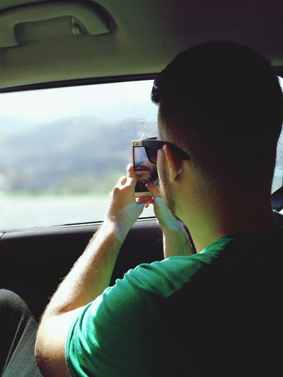 Close-up of man holding camera in car