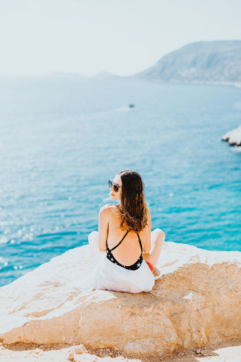 Water Rear View Leisure Activity One Person Sea Real People Lifestyles Scenics - Nature Adult Beauty In Nature Young Women Young Adult Tranquil Scene Women Hairstyle Day Tranquility Nature Sitting Hair Outdoors