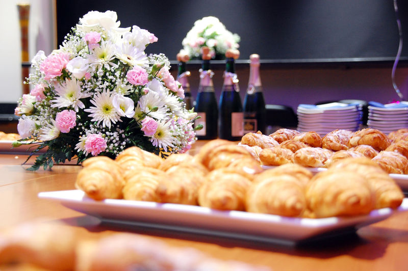 Close-up of croissants in plate with bouquet on table