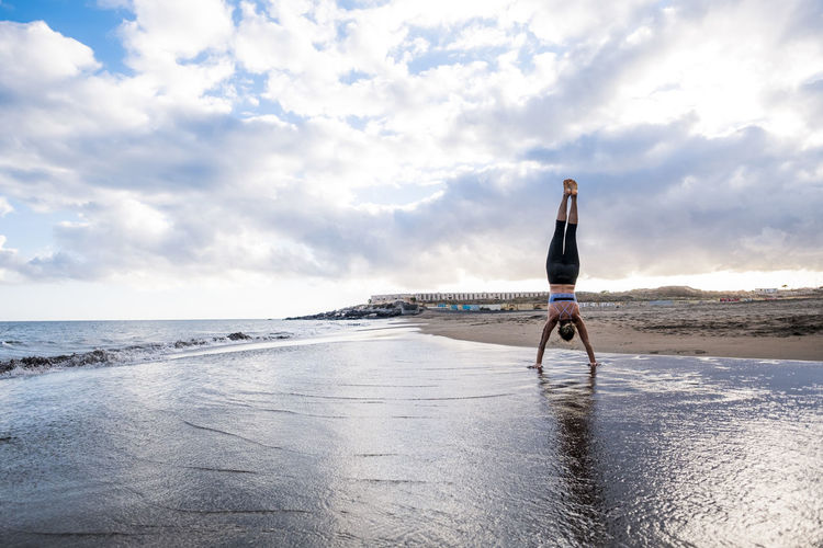 Full length of young woman doing handstand at beach against cloudy sky