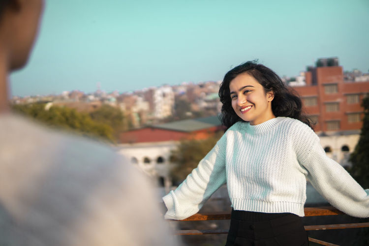 Smiling young woman standing by cityscape against sky