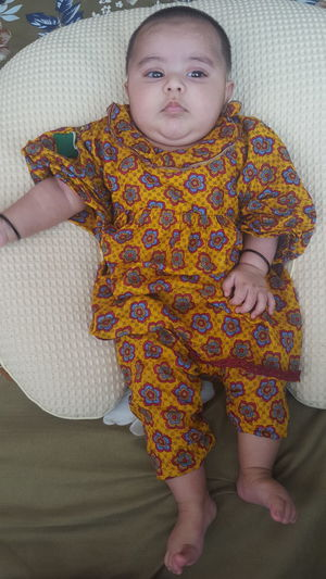 Midsection of baby girl relaxing on bed at home