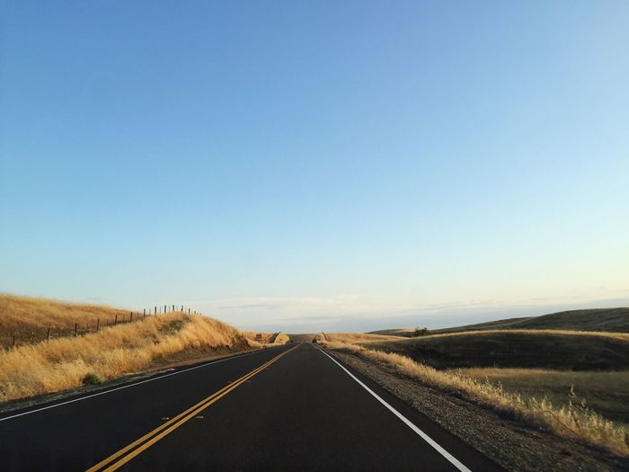 Empty Road By Field Against Clear Sky