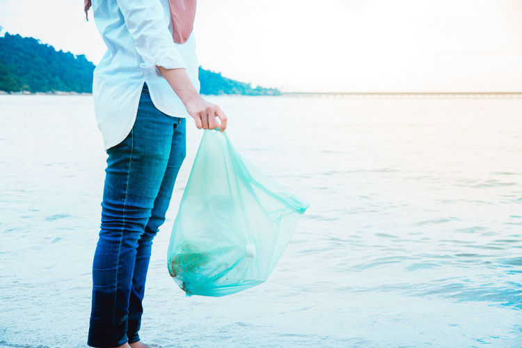 Low section of woman holding plastic at beach