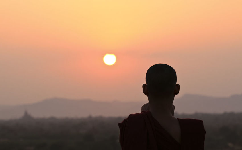 Rear View Of Monk Against Orange Sky During Sunset
