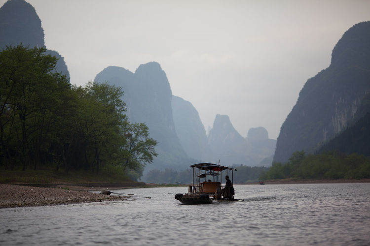 Passenger Boat On River In Mountains