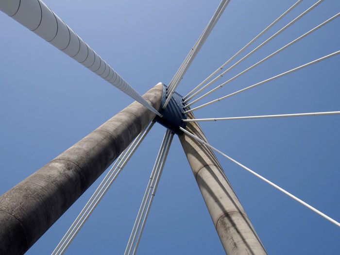 A close up of the supports and cables of the suspension bridge in southport against a blue sky