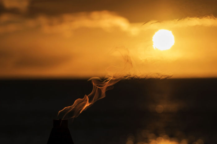 A Torch Flame Merges with Sunset Over Ocean on Horizon Flame Flames Gold Hawaii Orange Sunset Silhouettes Tropics Abstract Beauty In Nature Close-up Fire - Natural Phenomenon Focus On Foreground Horizon Over Water Nature No People Ocean Outdoors Scenics Sky Sunset Torch Tranquility Travel Destinations