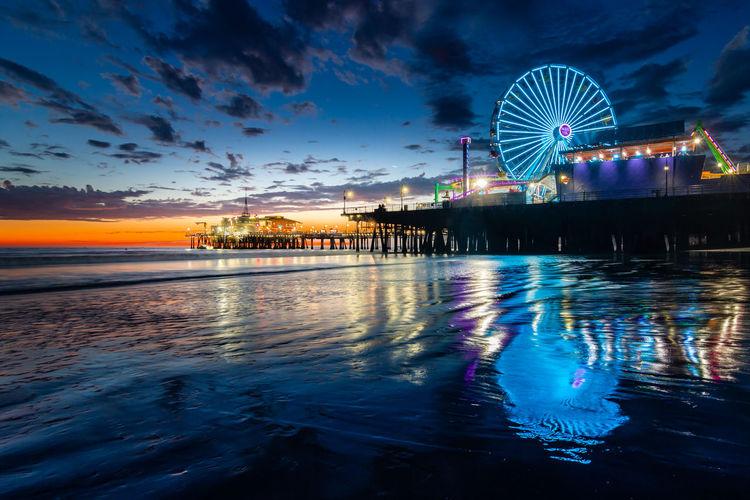 Illuminated ferris wheel by sea against sky at sunset