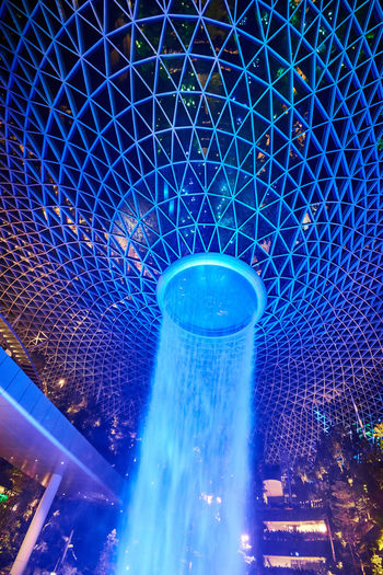 Jewel Changi Airport Water Vortex Fountain Blue Illuminated Architecture Night Built Structure Motion Indoors  No People Nature Lighting Equipment Light Nightlife City Enjoyment Arts Culture And Entertainment Light - Natural Phenomenon Low Angle View Ceiling