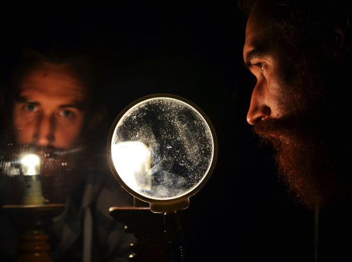 Man Holding Magnifying Glass Against Mirror In Darkroom
