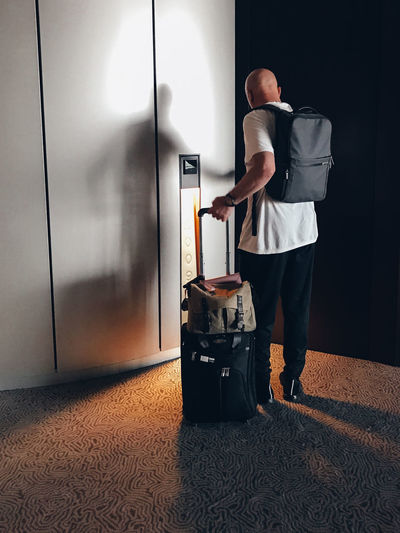 Tired traveller arriving at his room with luggage in tow and opening door of hotel room Travelling One Person Real People Luggage Full Length Entrance Travel Indoors  Door Standing Rear View Adult Lifestyles Suitcase Transportation Flooring Pushing Leisure Activity Hotel Shelter Unlocking Travels Backpack Man