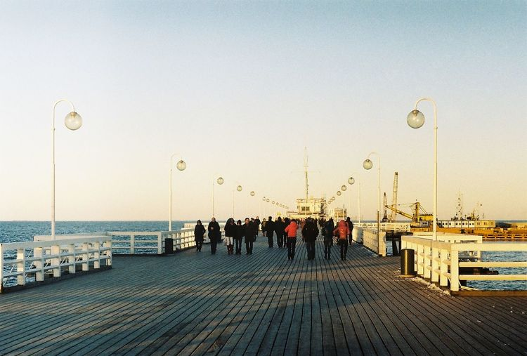 People On Pier Against Clear Sky