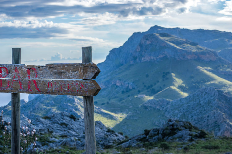 Old wooden road sign against mountain