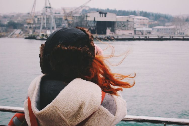 Rear view of woman leaning on railing in front of sea
