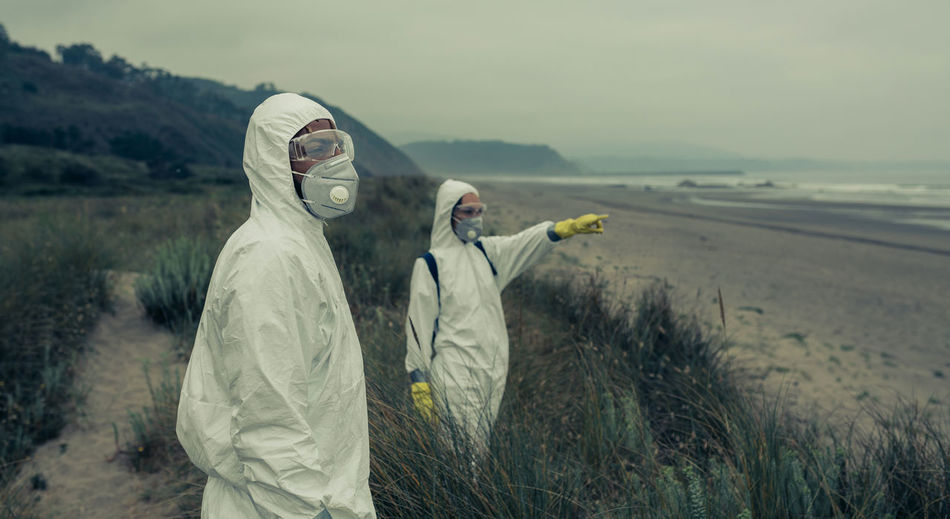 Man and woman wearing pollution mask while standing outdoors