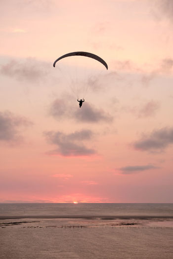 Low angle view of silhouette person paragliding over sea against sky during sunset