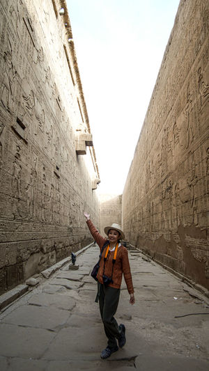 Full length of woman standing amidst wall