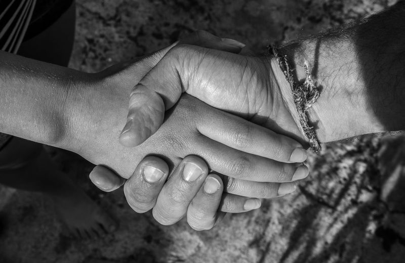 Close-up of people shaking hands outdoors