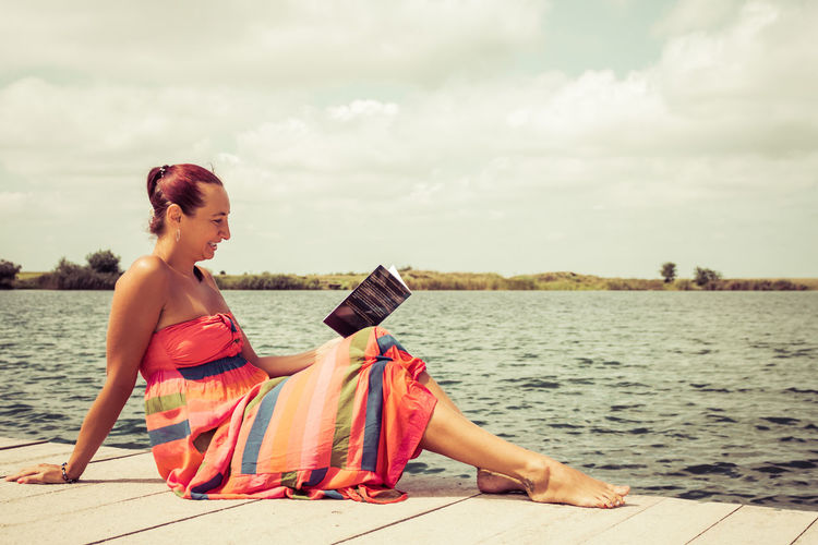 Smiling woman in sun dress reading book while sitting on a pier during summer day. copy space.