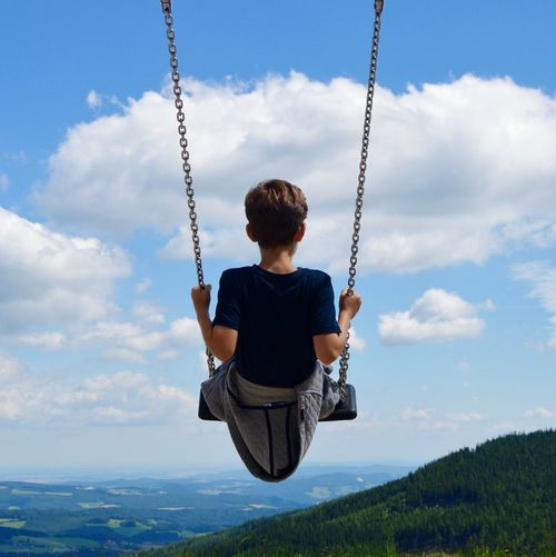 Rear view of boy on swing against cloudy sky