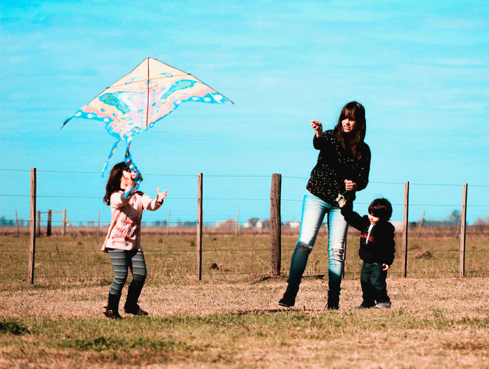 Woman flying kite with children on field against blue sky