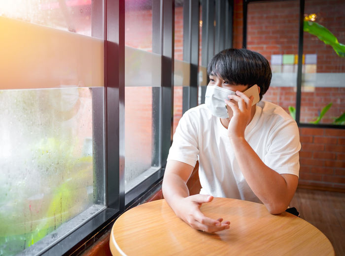 A handsome young teenage boy wear mask talkinging on smart mobile phone waiting in cafeteria.