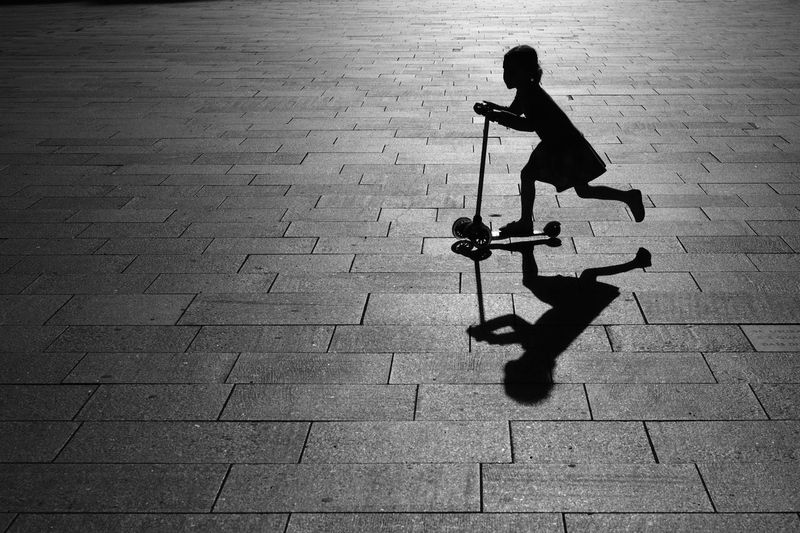 Silhouette of girl riding push scooter on pavement
