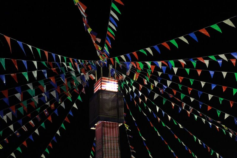 Low angle view of illuminated flags hanging at night