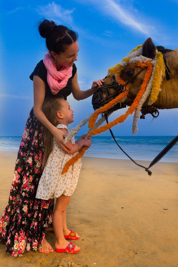 Loving mother spending a quality time with her daughter Beach Camel Childhood Elementary Age Enjoyment Full Length Girls Leisure Activity Lifestyles Mother And Daughter Person Sand Sea Shore Sky Sunlight Water Women Who Inspire You Young Women Color Of Life! Color Of Life