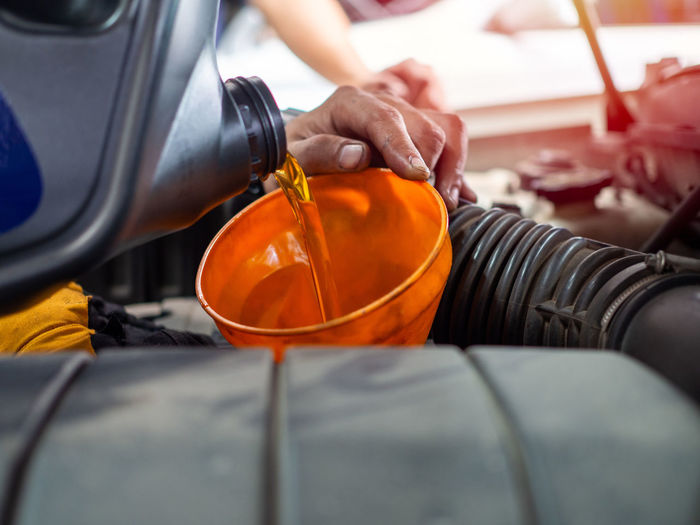 Cropped hands of person pouring oil in car engine