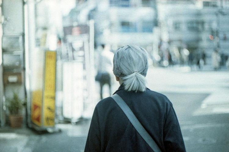 Rear view of woman standing on street in city