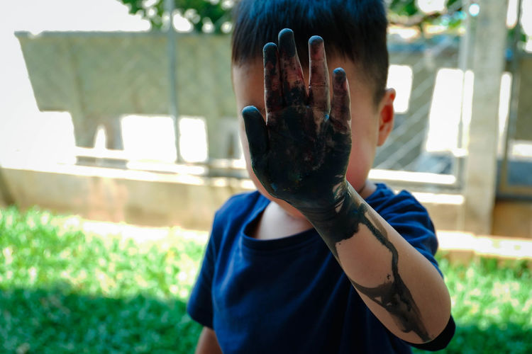 Close-up of boy with dirty hand
