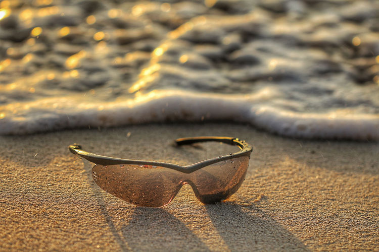 sunglasses Foam Sunglasses Protection UV Protection Beach Sunset Water Sunlight Gold Colored Sea Single Object Close-up Sand Sandy Beach Tranquil Scene Coast Tranquility